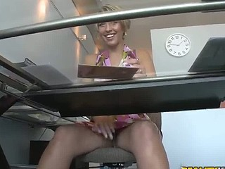 The gorgeous MILF masturbates her pussy under a table in the office