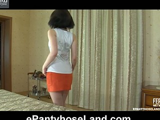 Black-haired chick puts on her sheer hose to go with her working outfit