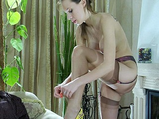 Slender-legged gal takes her time putting on her thin barely visible nylons