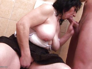 The bathroom is a room with many uses, and this older woman is using the toilet to sit on, masturbate, and suck her man's dick! Her young stud appreciates her skilled mouth and big tits, which he sucks on for a bit while stroking himself. Soon she's on her knees to continue giving head to her man.