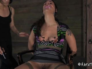 Tied on the chair with duct tape covering her mouth this brunette milf is at the mercy of her mistress. Her pussy is gaped with the help of some clamps and the mistress rubs it hard with a vibrator. Take a look at her, how powerless she is in front of that bitch. All that she can do is to obey!