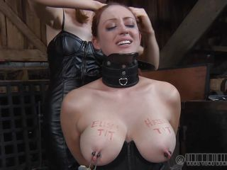 Slutty redhead Holly is all tied up with a big collar around her neck. The two men demanded one boob for each one of them and sticked metal clamps on her nipples, after writing their names on her tits. They tie her up and make her stand on her tip-toes. She looks so sexy and provocative. Don`t you think so?