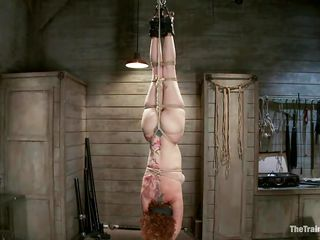 Pretty redhead with milky white skin and soft boobs is ready to take some dick! They play a little game, as she hangs there upside down and blindfolded she needs to find the dick and suck it. Being a whore she finds it immediately and starts on sucking the long hard penis. Look how lustfully she swallows that cock