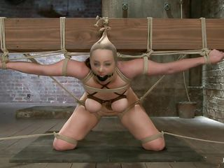 She really under the pressure! Bella is tied on that big wooden beam, ball gagged and with her boobs squeezed. Her mistress plays with those boobs and then goes behind her to play with her ass too. That booty is round and sexy and a big dildo inside it makes it look even better. How long will it be until she squirts?