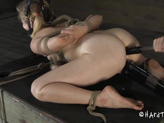 She is tied hard, and we like it that way. Watch the white blonde babe receiving all the humiliation and punishment she deserves. At first she is bent over and has two vibrators on her cunt but then things complicate and she is positioned with her legs up and her shaved pussy on display.